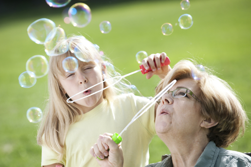 A little girl blowing bubbles with her grandmother.